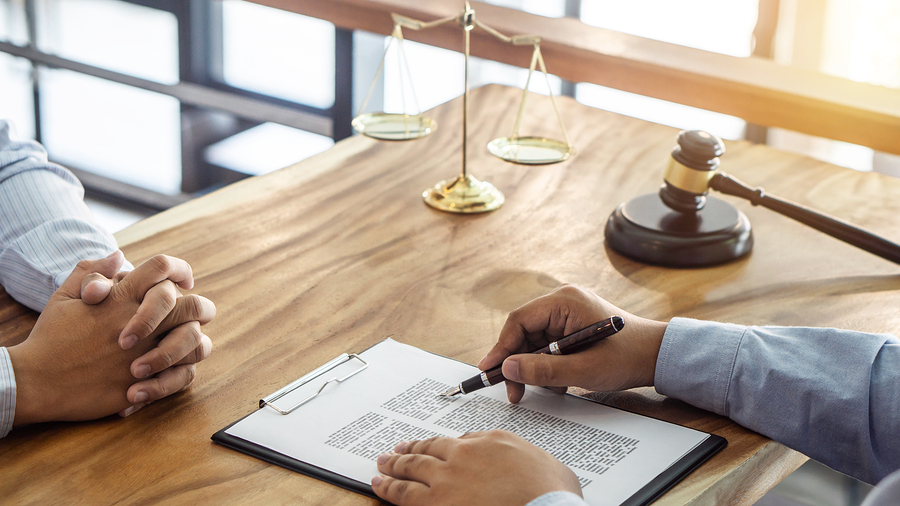 talking with a fort worth estate planning attorney at a wood desk with a gavel and scales of justice.