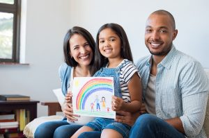 family with girl holding artwork symbolizing the child adoption process in Texas.